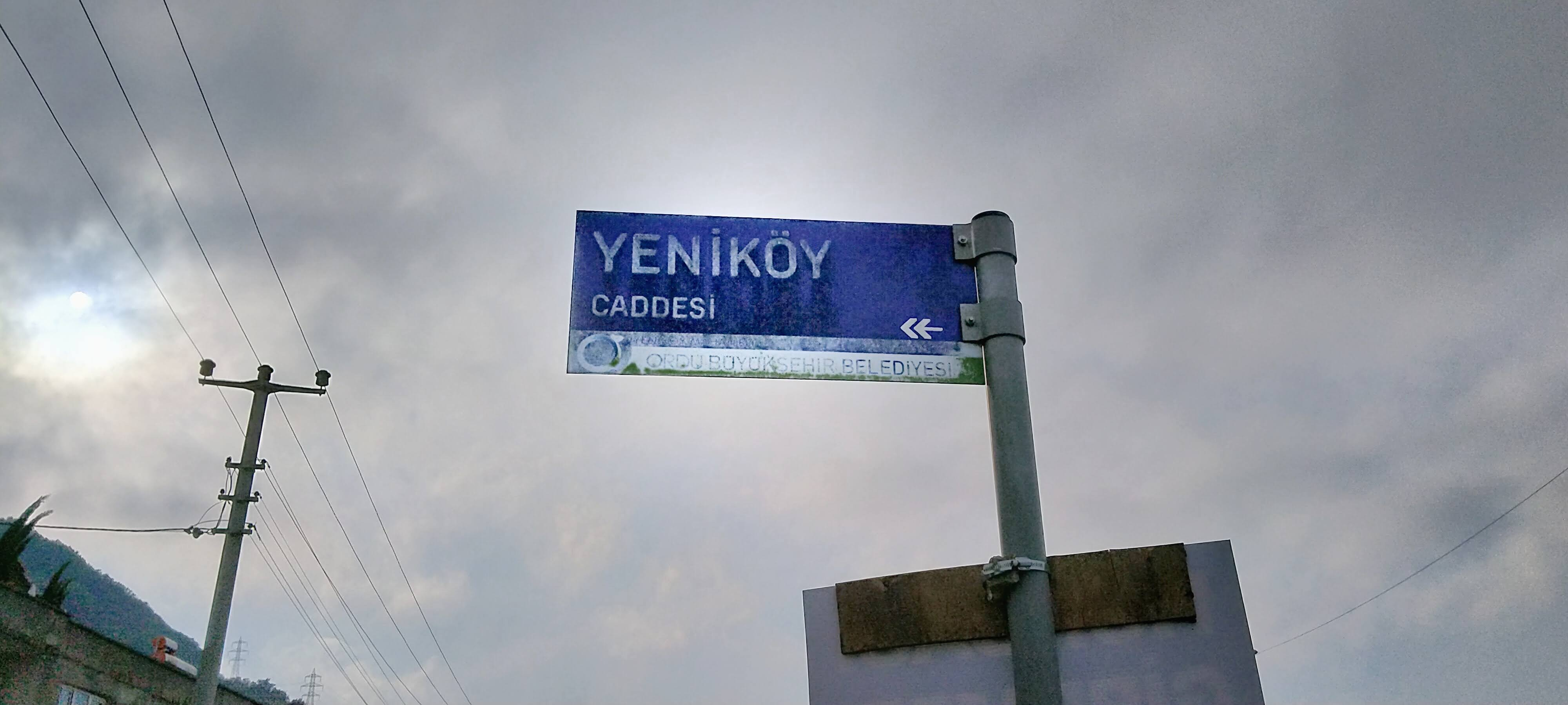 Old, fading street sign, with text 'Yeniköy Caddesi ↞' and the logo of the Metropolitan Municipality of Ordu.